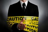 picture of extend  - image of a man wearing a suit with caution tape extending his hand to shake - JPG