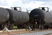 stock photo of railroad car  - Black tanker railroad cars containing oil wait to be unloaded on a side rail - JPG