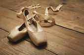 stock photo of ballet shoes  - Two old ballet shoes on wooden floor - JPG