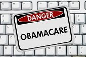 stock photo of mandate  - Computer keyboard keys with danger sign with word Obamacare Obamacare - JPG
