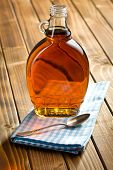 stock photo of maple syrup  - maple syrup in glass bottle on wooden table - JPG
