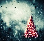 Christmas tree glowing on winter background with snow storm, frost, glittering lights. Vintage textu