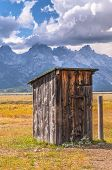 image of outhouses  - Outhouse in Mormon Row with Teton Range in background - JPG