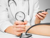 stock photo of sphygmomanometer  - Unrecognizable doctor measures blood pressure a patient by sphygmomanometer - JPG