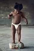 image of naked children  - Naked african baby with diaper standing in rural poverty stricken area - JPG