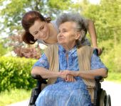 stock photo of disabled person  - Senior woman in a wheelchair with her granddaughter - JPG