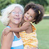 pic of grandma  - Portrait of a caucasian grandma carrying her little hispanic granddaughter - JPG
