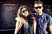 image of denim jeans  - Couple of young people in jeans clothes posing outdoors over brick wall - JPG