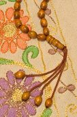 image of prayer beads  - Islamic prayer beads over prayer rug under studio lighting - JPG