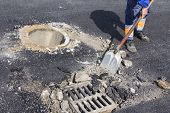 stock photo of manhole  - Utilities worker repairing sewer manhole cover in the road - JPG