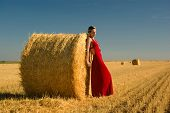 Girl In Red Evening Dress Leaning On Straw Bale.