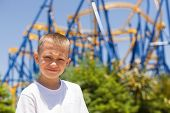 Boy on the background of the attraction roller coaster.
