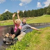 stock photo of luge  - Portrait of young couple enjoying summer sledge ride - JPG