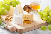 camembert cheese with grapes, honey and nuts on wooden background