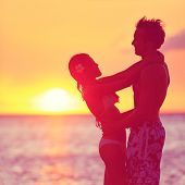 Romantic couple embracing kissing on beach at sunset. Two young lovers playful and happy together on