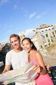 Tourists holding map by Roman Forum sightseeing on travel vacation in Rome, Italy. Happy tourist cou