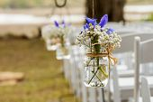 stock photo of mason  - flowers hanging in mason jar at wedding - JPG
