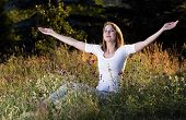 stock photo of breath taking  - Beautiful young woman taking a breath in blooming meadow - JPG