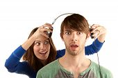 picture of interrupter  - Pretty young woman interrupts man with headphones - JPG