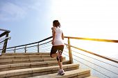 image of stepping stones  - Runner athlete running on seaside stone stairs - JPG