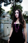 foto of burial-vault  - Pretty vampire near charnel house walking through graveyard  - JPG