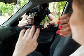stock photo of plunder  - Masked robber with gun threatens a woman in car - JPG