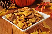 foto of pine cone  - A bowl of snack mix on a holiday table with a pumpkin pine cones and autumn leaves - JPG