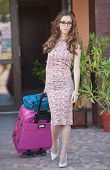 image of carry-on luggage  - Beautiful woman with suitcases leaving the hotel in a big city - JPG