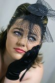 picture of fascinator  - A lady wearing a black fascinator and gloves  - JPG