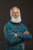 stock photo of long beard  - old man with a long beard with big smile on a dark background - JPG
