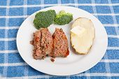 stock photo of meatloaf  - Slices of home made meatloaf with a hot buttered baked potato and fresh broccoli - JPG