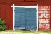 pic of red barn  - Red painted barn with two blue painted doors - JPG