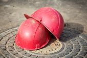 pic of manhole  - Close-up of the two red helmets on the manhole