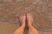 picture of wet feet  - Bare female feet on the shore washed by the sea - JPG
