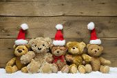 stock photo of teddy  - Five teddy bears with Christmas hats on wooden background - JPG