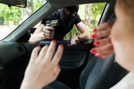stock photo of unsafe  - Masked robber with gun threatens a woman in car - JPG