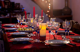 picture of christmas dinner  - A table prepared for christmas party with red napkin blue trasparent glasses and white and gold plates - JPG