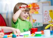 picture of daycare  - kids playing with play clay at home or  playschool - JPG