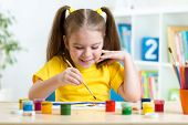 stock photo of day care center  - smiling kid girl painting with paintbrush at home or day care center - JPG