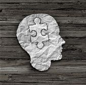 picture of wood pieces  - Puzzle head solution concept as a human face profile made from crumpled white paper with a jigsaw piece cut out inside the brain area on an old wood background as a mental health symbol - JPG