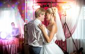 stock photo of married  - Beautiful newly married couple dancing at colorful lights and flares - JPG