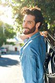 image of walking away  - Portrait of a smiling man walking away with bag - JPG