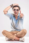picture of fingers crossed  - Happy young fashion man sitting with his legs crossed while holding one hand on his hat and showing thumbs up gesture with the other hand - JPG