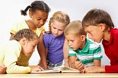 stock photo of girl reading book  - Portrait of pupils looking at page of encyclopaedia at reading lesson - JPG