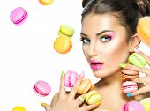 picture of lipstick  - Beauty fashion model girl with colourful makeup and manicure taking colorful macaroons - JPG