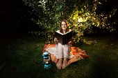 stock photo of night gown  - Young smiling woman sitting on grass at night and reading big old book - JPG
