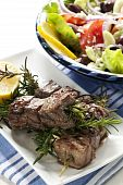 stock photo of greek food  - Lamb kebabs grilled on rosemary skewers with Greek salad - JPG