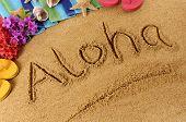stock photo of starfish  - The word Aloha written on a sandy beach with flowers beach towel starfish and flip flops - JPG