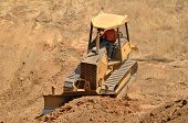 image of bulldozer  - Small bulldozer clearing dirt from a hillside in preperation for a new commerical construction development - JPG