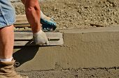 stock photo of masonic  - Concrete mason contractor using finishing trowel at a new commercial residential development project - JPG